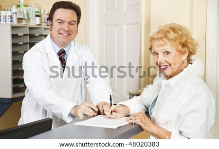 Doctor helps senior patient with her medical forms. - stock photo