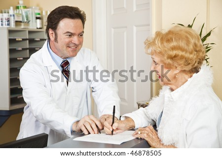 Doctor helps senior woman fill out paperwork in his office. - stock photo