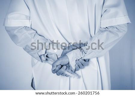 Doctor hide behind syringe on back ,holding in  hands. Medical concept. - stock photo