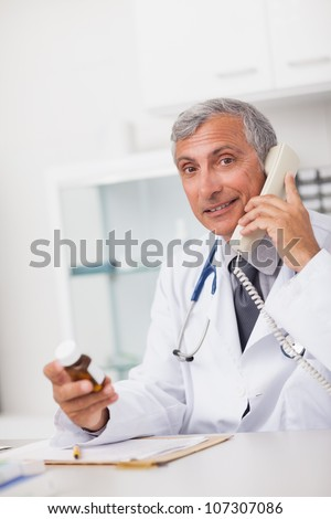 Doctor holding a drug box and a phone while sitting in a medical office - stock photo