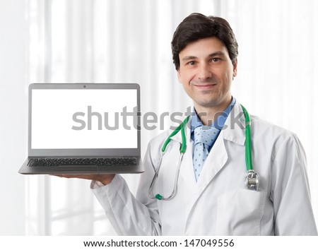 doctor holding a laptop computer with blank screen, isolated on a white background.  - stock photo