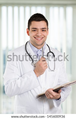 Doctor holding a pen and repotrts and smiling at you.