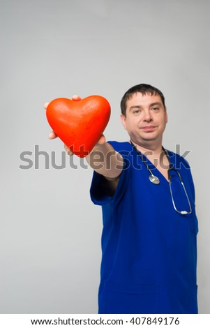 Doctor holding a red heart - stock photo