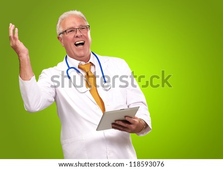 Doctor Holding A Tablet And Happy On Green Background - stock photo