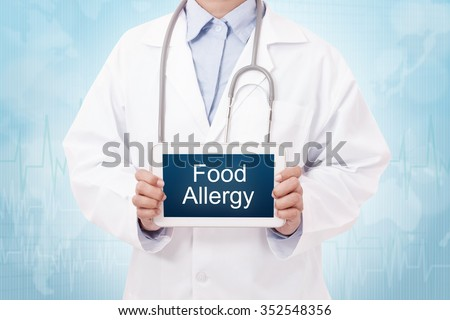 Doctor holding a tablet pc with Food Allergy sign on the display - stock photo