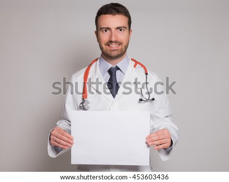 doctor holding a white cardboard banner isolated on gray background - stock photo