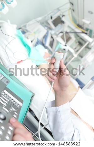 doctor holding an ultrasound examination of the patients in the ICU - stock photo