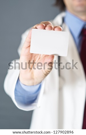 Doctor holding blank business card. Shallow depth of field, focus on hand and a card. - stock photo