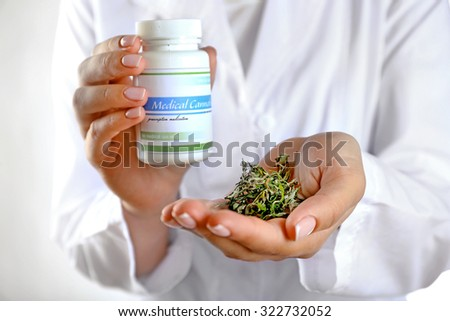 Doctor holding bottle of medical cannabis and dry herbs close up - stock photo
