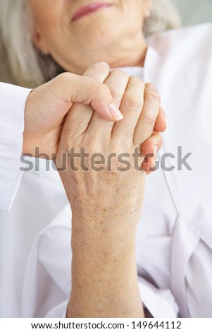 Doctor holding hand of senior woman patient for comfort in a hospital - stock photo