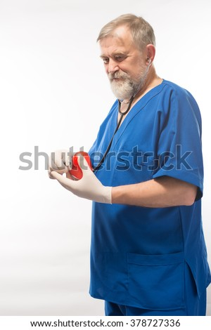 Doctor holding heart - stock photo