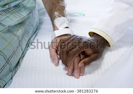 Doctor holding patients hand - stock photo