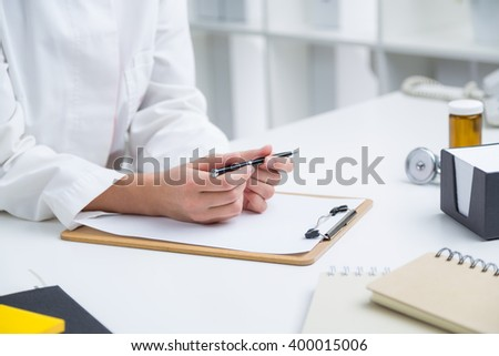 Doctor holding pen ready to make notes, only hands seen. Office. Concept of work. - stock photo