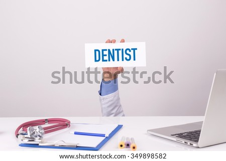 Doctor Holding Placard written DENTIST