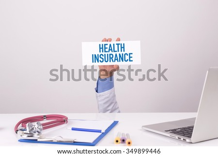 Doctor Holding Placard written HEALTH INSURANCE