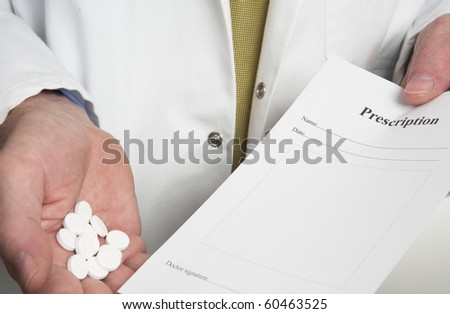 Doctor holding prescription and pills - stock photo