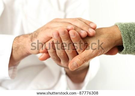 Doctor holding senior's hands - stock photo