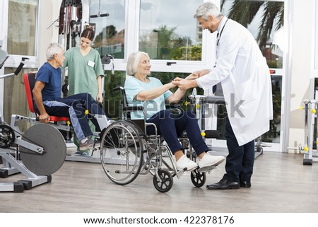 Doctor Holding Senior Woman's Hands In Wheelchair - stock photo