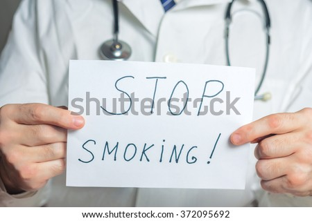 Doctor holds a clipboard with stop smoking label