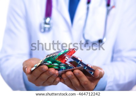 doctor holds the patient's hand with pills