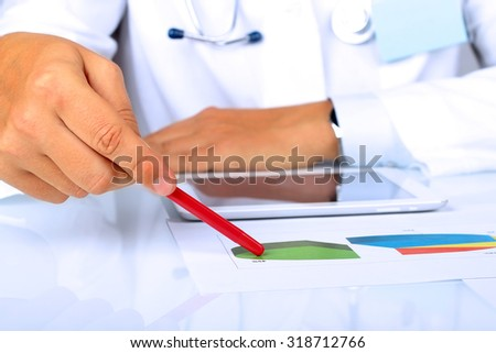 Doctor  in a white labcoat showing something on a graphs - stock photo