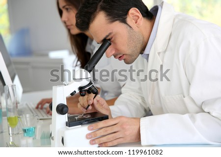 Doctor in biology working on microscope - stock photo