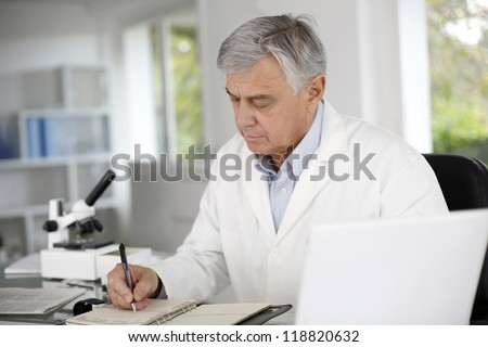 Doctor in biology writing report on agenda - stock photo