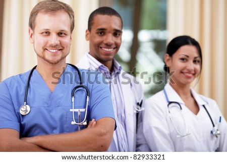 Doctor in blue scrubs with his colleagues behind
