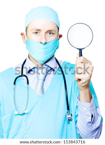 Doctor in gown and mask holding a magnifying glass in his hand conceptual of undergoing a medical examination and investigation - stock photo
