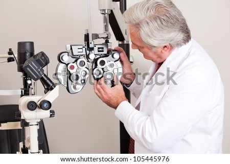 Doctor in ophthalmology clinic adjusting phoropter. - stock photo