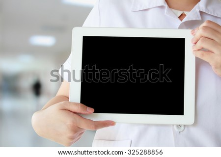 Doctor in white coat showing blank digital tablet computer with hospital interior corridor background - stock photo