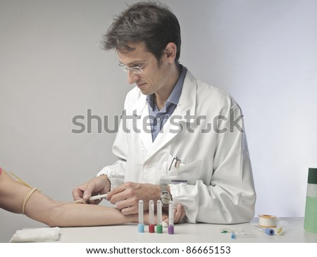 Doctor injecting some vaccine in a man's arm - stock photo