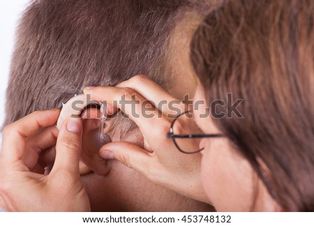 Doctor inserting a hearing aid in an ear of a senior man