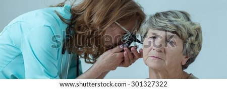 Doctor is checking elder lady ear with otoscope - stock photo