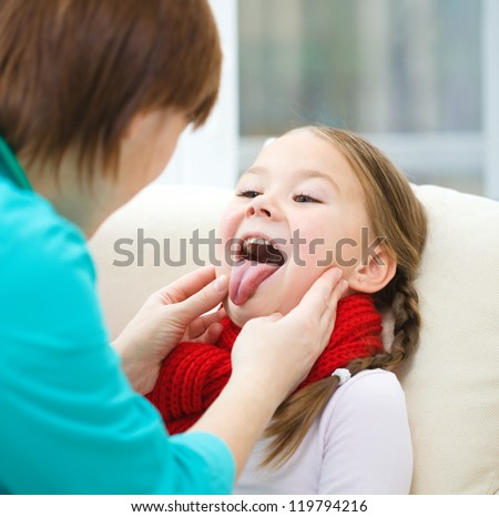 Doctor is examining a little girl who showing tongue, indoor shoot - stock photo