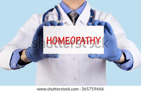 Doctor keeps a card with the name of the diagnosis -?? homeopathy. Selective focus. Medical concept. - stock photo
