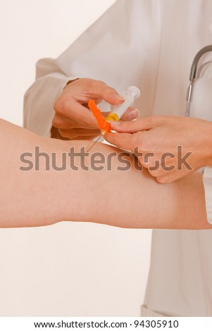 Doctor knows just pulls in a syringe for a patient to /Doctor and the syringe - stock photo