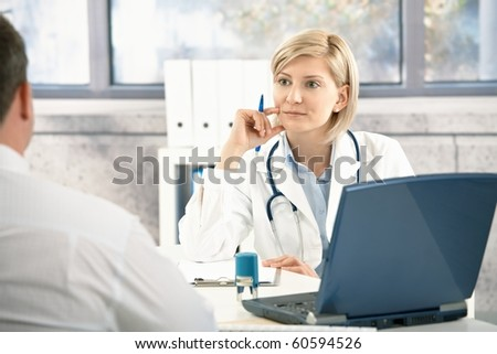 Doctor listening to patient with concentration, sitting at desk in office.? - stock photo