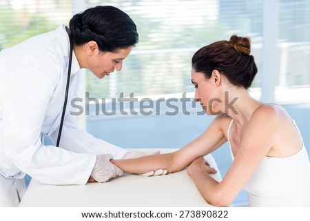 Doctor looking at her patients arm in medical office - stock photo
