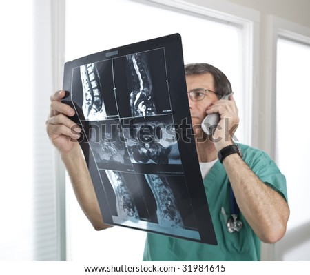 Doctor looking at radiology scan. Short depth of field. Focus on MRI/Xray film. Doctor out of focus. - stock photo