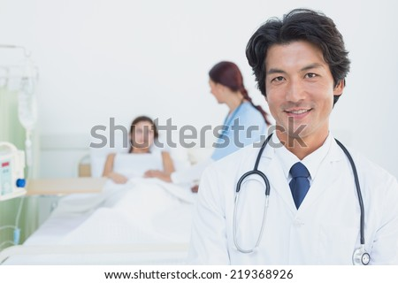 Doctor looking at the camera in front of a patient - stock photo
