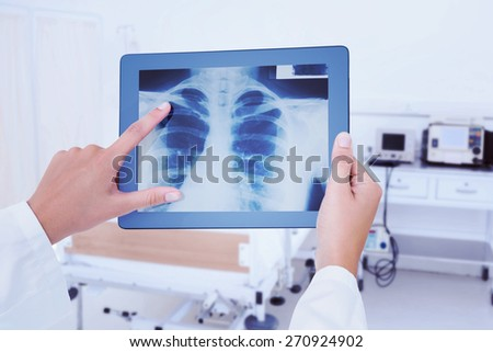 Doctor looking at xray on tablet against empty bed in the hospital room - stock photo