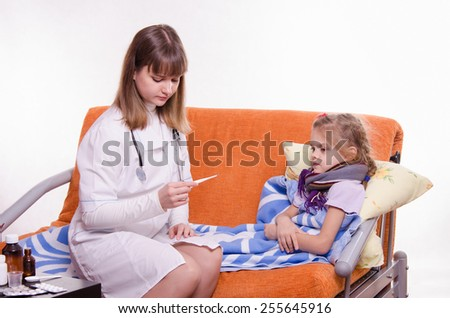 Doctor looking baby temperature on a thermometer - stock photo