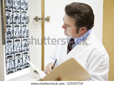 Doctor looks at CAT scan and makes notes in a patient's chart. - stock photo