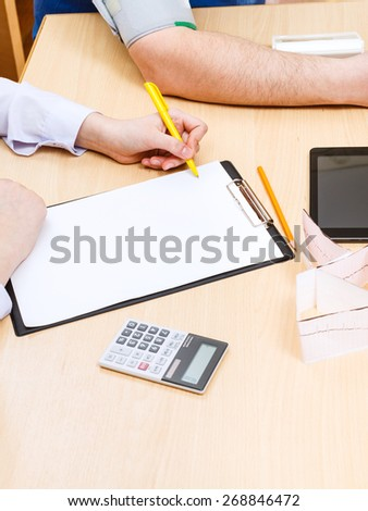 doctor makes appointment and measures blood pressure of patient - stock photo