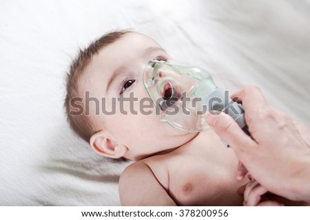 Doctor makes inhalation to a sick little baby. Healthcare and medicine concept at pediatrician department.
