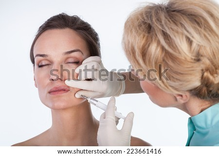 Doctor making an injection in beauty clinic - stock photo