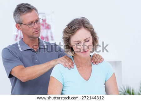 Doctor massaging his patient shoulders in medical office - stock photo