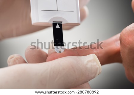 Doctor Measuring Sugar Reading Of Patient With Glucometer - stock photo