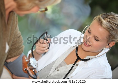 Doctor measuring the blood pressure of a patient - stock photo